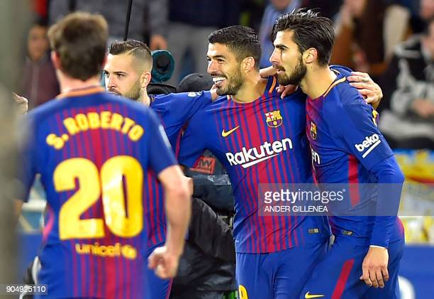 Barcelona's Uruguayan forward Luis Suarez celebrates a goal with Barcelona's Portuguese midfielder Andre Gomes and Barcelona's Spanish defender Jordi...