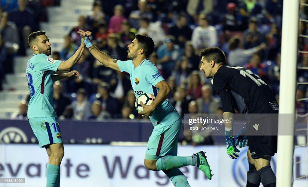 Barcelona's Uruguayan forward Luis Suarez (C) celebrates a goal with Barcelona's defender Jordi Alba (L) during the Spanish league football match between Levante and Barcelona at the Ciutat de Valencia stadium in Valencia on May 13, 2018.