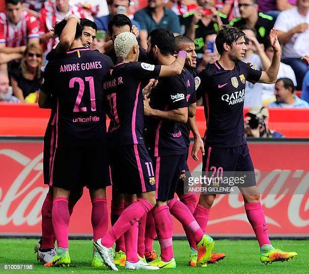 Barcelona's Uruguayan forward Luis Suarez celebrates a goal with teammates during the Spanish league football match Real Sporting de Gijon vs FC...