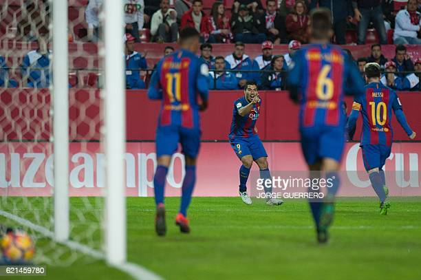 Barcelona's Uruguayan forward Luis Suarez celebrates a goal with teammates during the Spanish league football match Sevilla FC vs FC Barcelona at the...