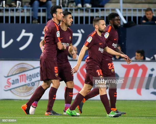 Barcelona's Uruguayan forward Luis Suarez celebrates a goal with teammates during the Spanish league football match between Malaga CF and FC...