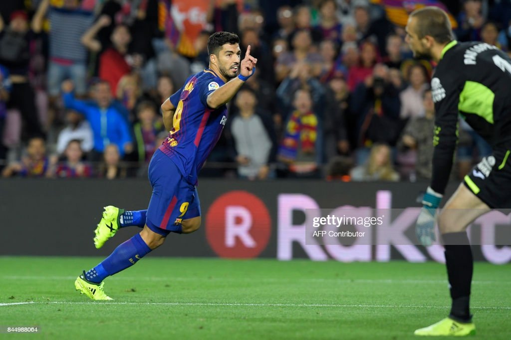 Barcelona's Uruguayan forward Luis Suarez (L) celebrates after scoring against Espanyol's goalkeeper Pau Lopez (R) during the Spanish Liga football match Barcelona vs Espanyol at the Camp Nou stadium in Barcelona on September 9, 2017. /