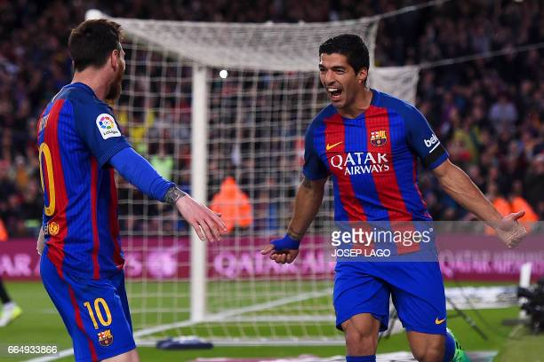 Barcelona's Uruguayan forward Luis Suarez celebrates his goal with Barcelona's Argentinian forward Lionel Messi during the Spanish league football...
