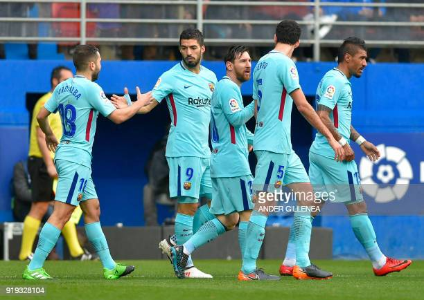 Barcelona's Uruguayan forward Luis Suarez celebrates scoring the opening goal with teammates during the Spanish league football match between SD...