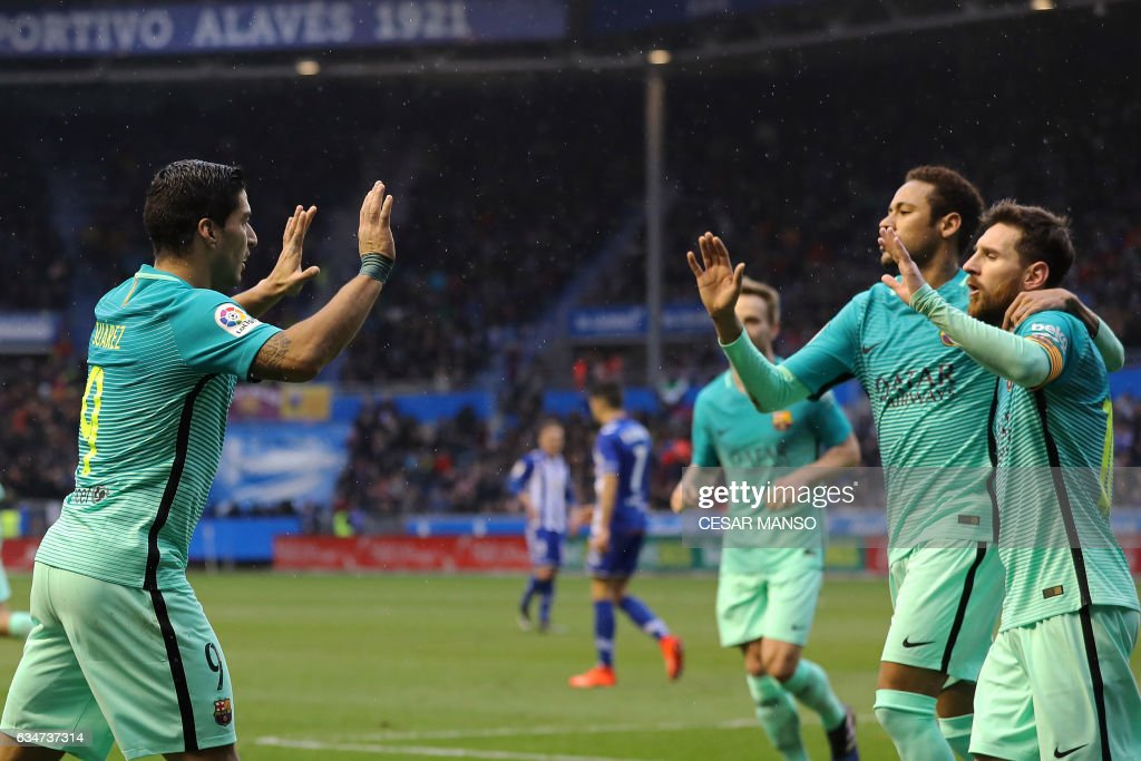 TOPSHOT - Barcelona's Uruguayan forward Luis Suarez (L) celebrates with Barcelona's Argentinian forward Lionel Messi (R) and Barcelona's Brazilian forward Neymar during the Spanish league football match Deportivo Alaves vs FC Barcelona at the Mendizorroza stadium in Vitoria on Feburary 11, 2017. /