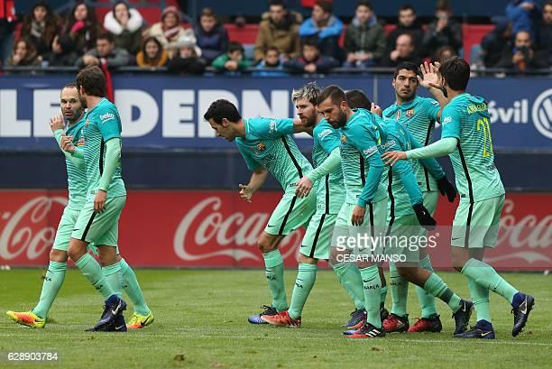 Barcelona's Uruguayan forward Luis Suarez celebrates with teammates during the Spanish league football match CA Osasuna vs FC Barcelona at the Reyno...