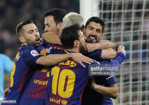 Barcelona's Uruguayan forward Luis Suarez celebrates with teammates after scoring a goal during the Spanish league football match between Real Betis...