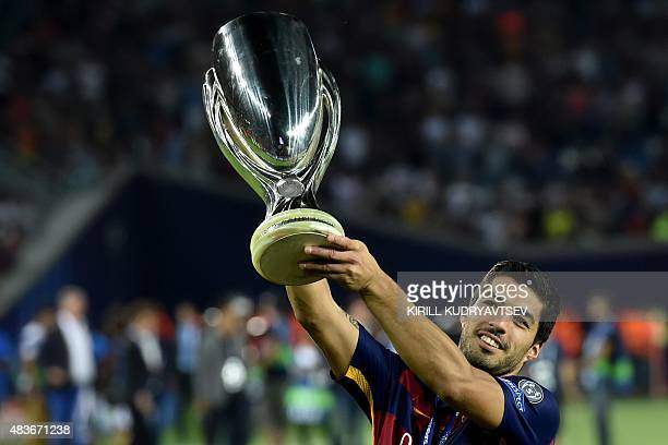 Barcelona's Uruguayan forward Luis Suarez celebrates with the trophy after winning the UEFA Super Cup final football match between FC Barcelona and...