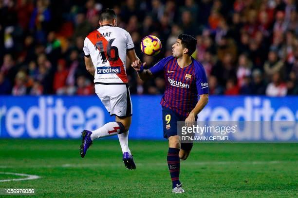 Barcelona's Uruguayan forward Luis Suarez challenges Rayo Vallecano's Spanish defender Jordi Amat during the Spanish league football match between...