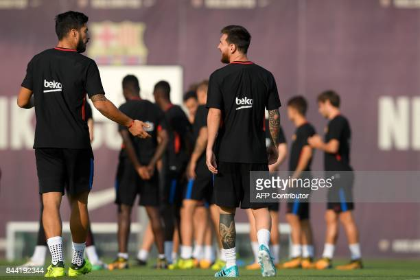 Barcelona's Uruguayan forward Luis Suarez chats with Barcelona's Argentinian forward Lionel Messi during a training session at the Sports Center FC...