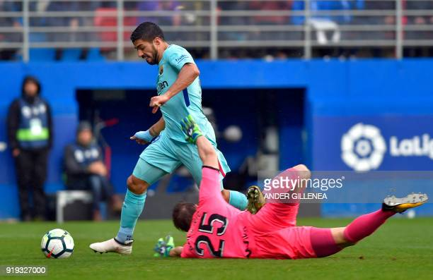 Barcelona's Uruguayan forward Luis Suarez dodges Eibar's Portuguese Serbian goalkeeper Marko Dmitrovic to score a goal during the Spanish league...