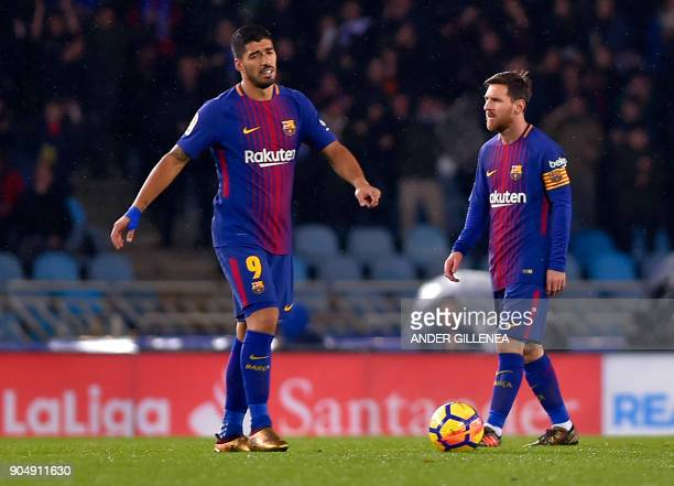 Barcelona's Uruguayan forward Luis Suarez gestures beside Argentinian forward Lionel Messi following Real Sociedad's opening goal during the Spanish...