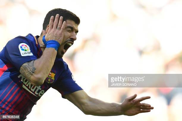 Barcelona's Uruguayan forward Luis Suarez gestures in pain during the Spanish League 'Clasico' football match Real Madrid CF vs FC Barcelona at the...
