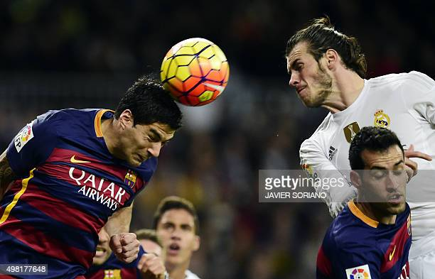 Barcelona's Uruguayan forward Luis Suarez heads the ball next to Real Madrid's Welsh forward Gareth Bale and teammate Barcelona's midfielder Sergio...
