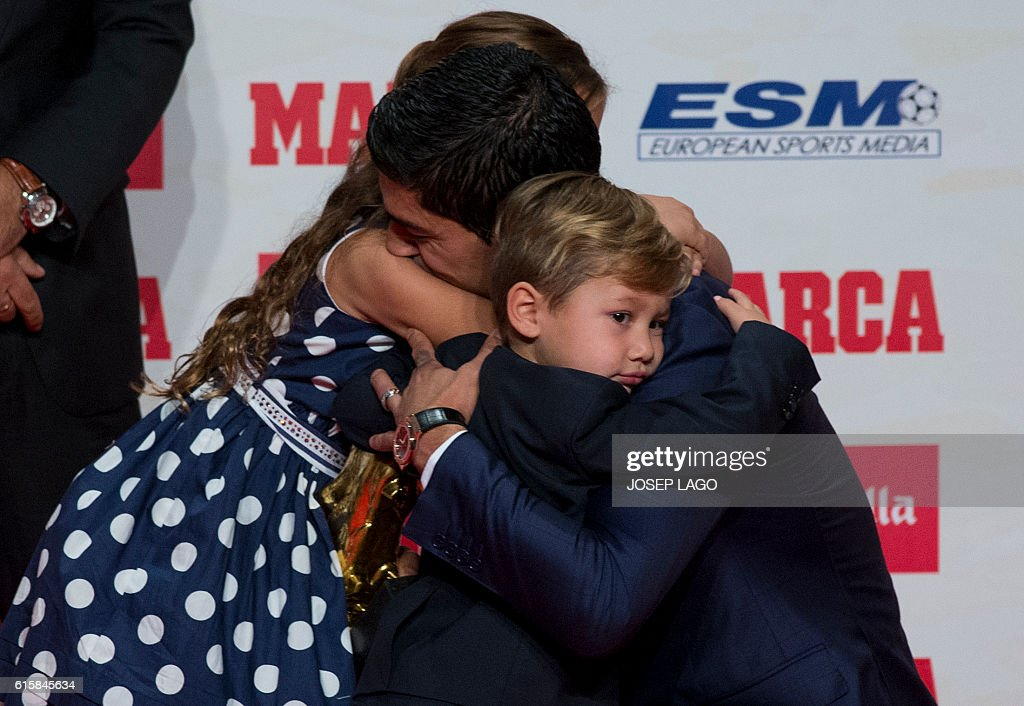 Barcelona's Uruguayan forward Luis Suarez (C) hugs his children Delfina and Benjamin (R), after receiving the 2015-2016 Golden Shoe award to the leading goalscorer in league matches from the top division of every European national league, on October 20, 2016 in Barcelona. / AFP / JOSEP