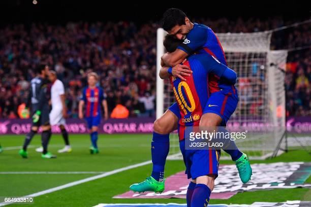 Barcelona's Uruguayan forward Luis Suarez is congratulated by Barcelona's Argentinian forward Lionel Messi after scoring a goal during the Spanish...