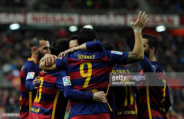 Barcelona's Uruguayan forward Luis Suarez is congratulated by teammates after scoring a goal during the Spanish league football match Real Sporting...