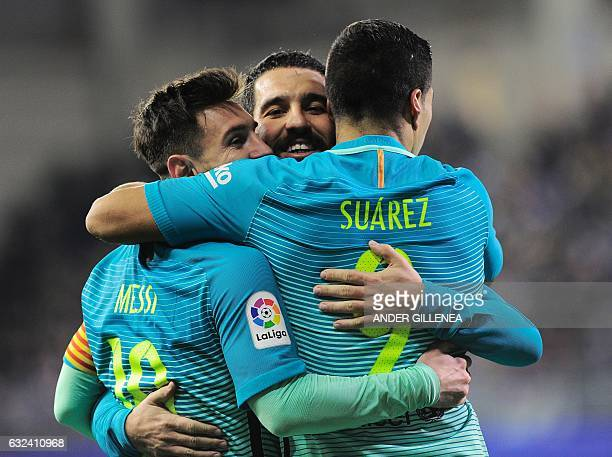 Barcelona's Uruguayan forward Luis Suarez is congratulated by teammates Argentinian forward Lionel Messi and Turkish midfielder Arda Turan after...
