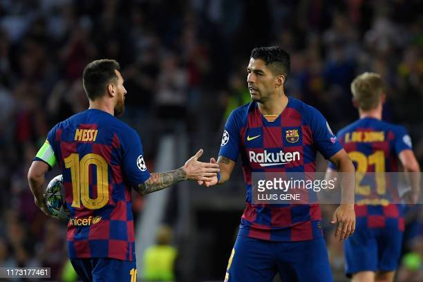 Barcelona's Uruguayan forward Luis Suarez is congratulated by teammate Barcelona's Argentine forward Lionel Messi after scoring a goal during the...
