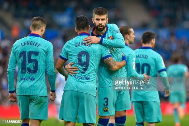 Barcelona's Uruguayan forward Luis Suarez is congratulated by teammate Barcelona's Spanish defender Gerard Pique after scoring a goal during the...
