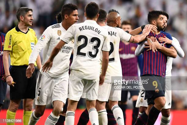 Barcelona's Uruguayan forward Luis Suarez is hold by Real Madrid's Spanish midfielder Isco during the Spanish league football match between Real...