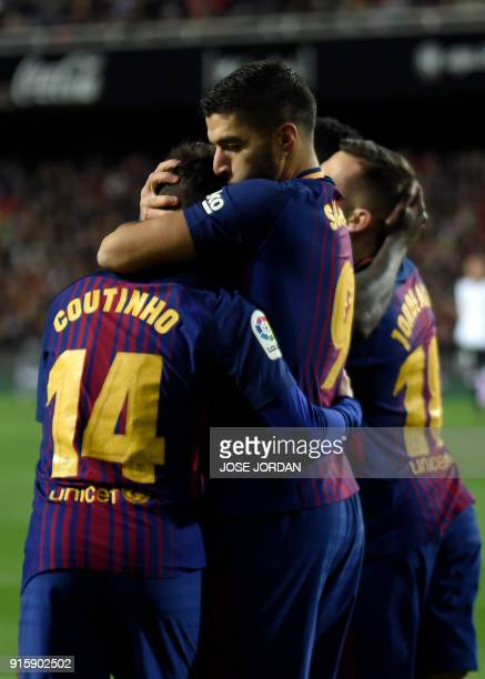 Barcelona's Uruguayan forward Luis Suarez kisses Barcelona's Brazilian midfielder Philippe Coutinho to congratulate him for his goal during the...