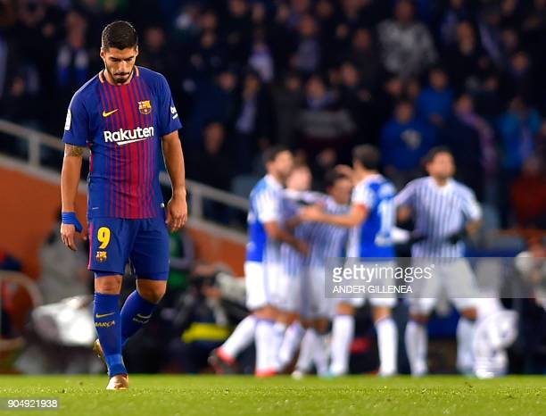 Barcelona's Uruguayan forward Luis Suarez looks downwards as Real Sociedad players celebrate their second goal during the Spanish league football...