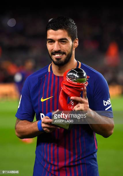 Barcelona's Uruguayan forward Luis Suarez poses with his Best Player of the Month award before the Spanish league football match between FC Barcelona...