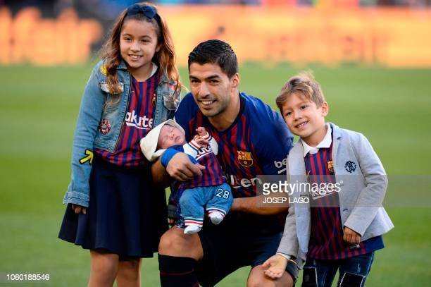 Barcelona's Uruguayan forward Luis Suarez poses with his three children after being awarded with La Liga's Player of the Month award for October...