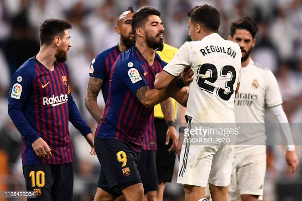 Barcelona's Uruguayan forward Luis Suarez pushes Real Madrid's Spanish defender Sergio Reguilon during the Spanish league football match between Real...
