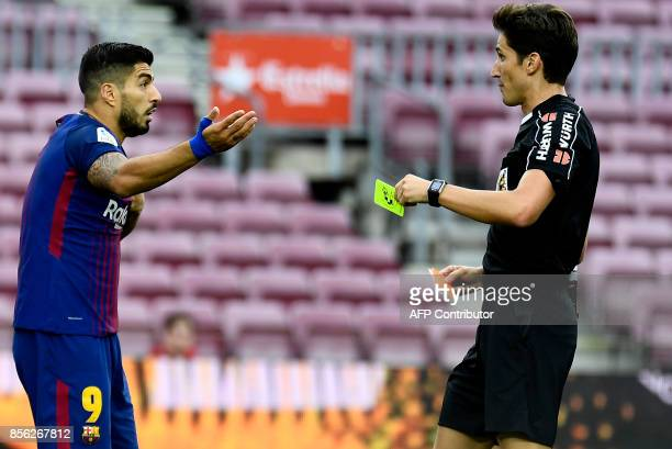 Barcelona's Uruguayan forward Luis Suarez reacts as he is booked by referee Jose Luis Munuera Montero during the Spanish league football match FC...