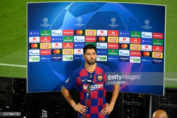 Barcelona's Uruguayan forward Luis Suarez reacts as he speaks to the press at the end of the UEFA Champions League round of 16 second leg football...