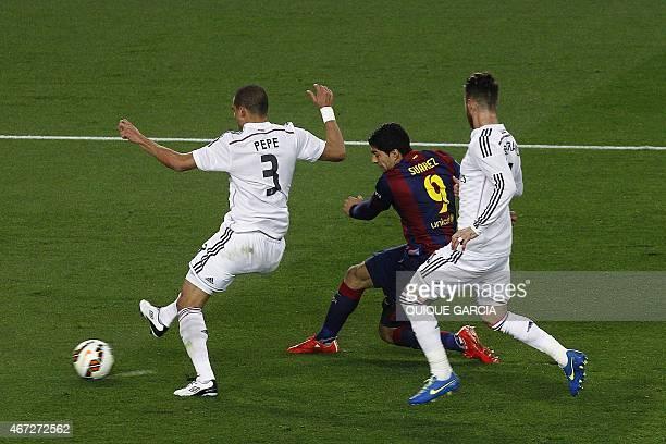 Barcelona's Uruguayan forward Luis Suarez scores a goal past Real Madrid's Portuguese defender Pepe and Real Madrid's defender Sergio Ramos during...
