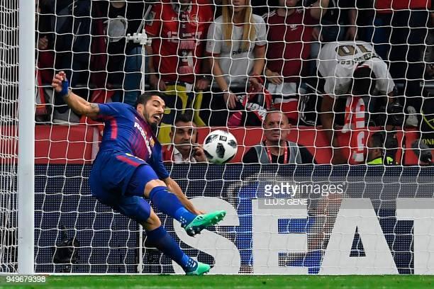 Barcelona's Uruguayan forward Luis Suarez scores during the Spanish Copa del Rey final football match Sevilla FC against FC Barcelona at the Wanda...