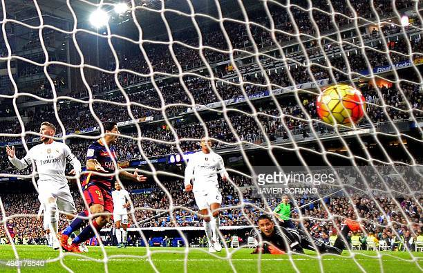 Barcelona's Uruguayan forward Luis Suarez shoots to score a goal next to Real Madrid's defender Sergio Ramos during the Spanish league 'Clasico'...