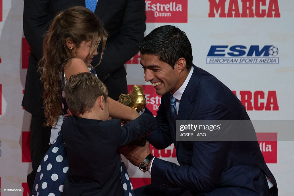Barcelona's Uruguayan forward Luis Suarez (R) shows to his children Delfina (L) and Benjamin, his new 2015-2016 Golden Shoe award to the leading goalscorer in league matches from the top division of every European national league, on October 20, 2016 in Barcelona. / AFP / JOSEP