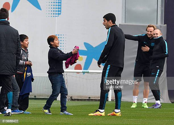 Barcelona's Uruguayan forward Luis Suarez signs autographs for children who gate-crashed the training session at the Sports Center FC Barcelona Joan...