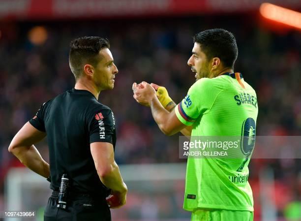 Barcelona's Uruguayan forward Luis Suarez speaks with Spanish referee Carlos del Cerro Grande during the Spanish league football match Athletic Club...