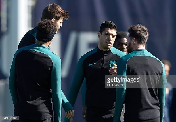 Barcelona's Uruguayan forward Luis Suarez talks with Barcelona's Argentinian forward Lionel Messi , Barcelona's defender Gerard Pique and Barcelona's...