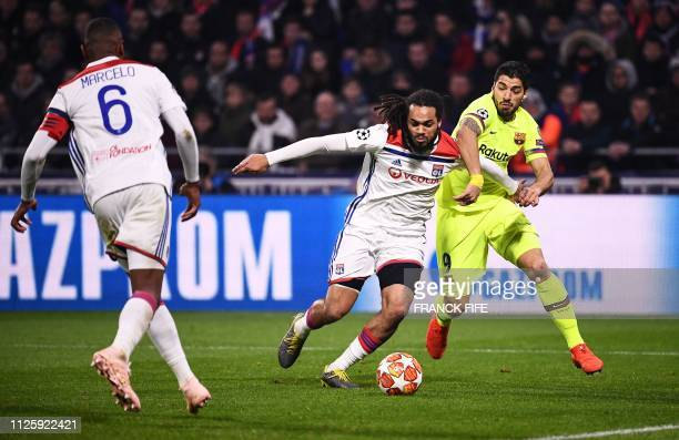Barcelona's Uruguayan forward Luis Suarez vies for the ball with Lyon's Belgian defender Jason Denayer during the UEFA Champions League round of 16...