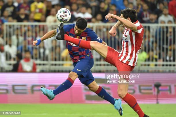 TOPSHOT Barcelona's Uruguayan forward Luis Suarez vies for the ball with Atletico Madrid's Montenegrin defender Stefan Savic during the Spanish Super...