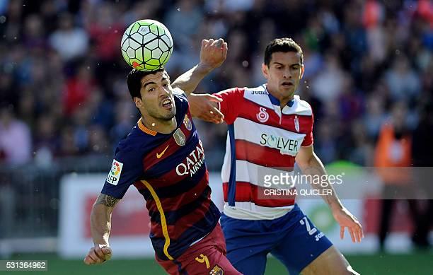 Barcelona's Uruguayan forward Luis Suarez vies for the ball with Granada's Gabonese defender Yrondu MusavuKing during the Spanish league football...