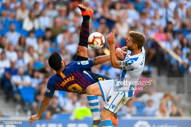 TOPSHOT Barcelona's Uruguayan forward Luis Suarez vies for the ball with Real Sociedad's Spanish midfielder Asier Illarramendi during the Spanish...