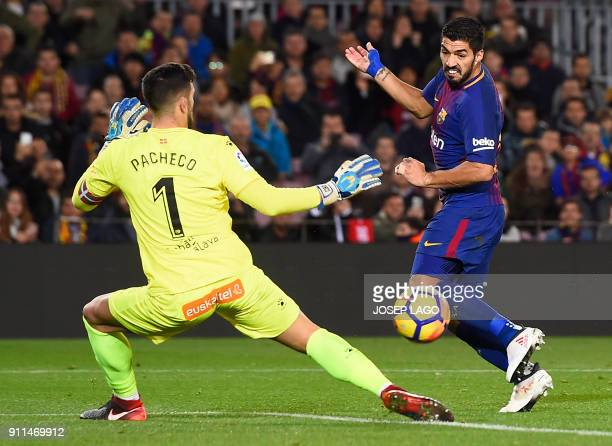 Barcelona's Uruguayan forward Luis Suarez vies with Alaves' Spanish goalkeeper Fernando Pacheco to miss a goal opportunity during the Spanish league...