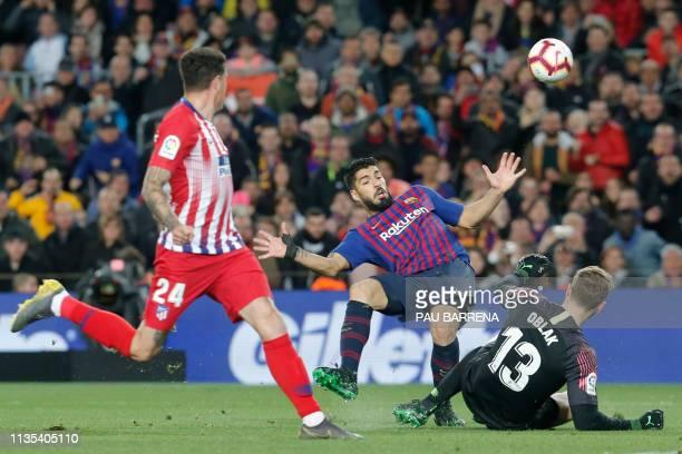 Barcelona's Uruguayan forward Luis Suarez vies with Atletico Madrid's Slovenian goalkeeper Jan Oblak during the Spanish league football match between...