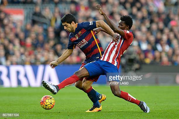 Barcelona's Uruguayan forward Luis Suarez vies with Atletico Madrid's Ghanaian midfielder Thomas Partey during the Spanish league football match FC...