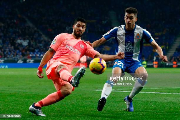 Barcelona's Uruguayan forward Luis Suarez vies with Espanyol's Spanish midfielder Marc Roca during the Spanish league football match RCD Espanyol...
