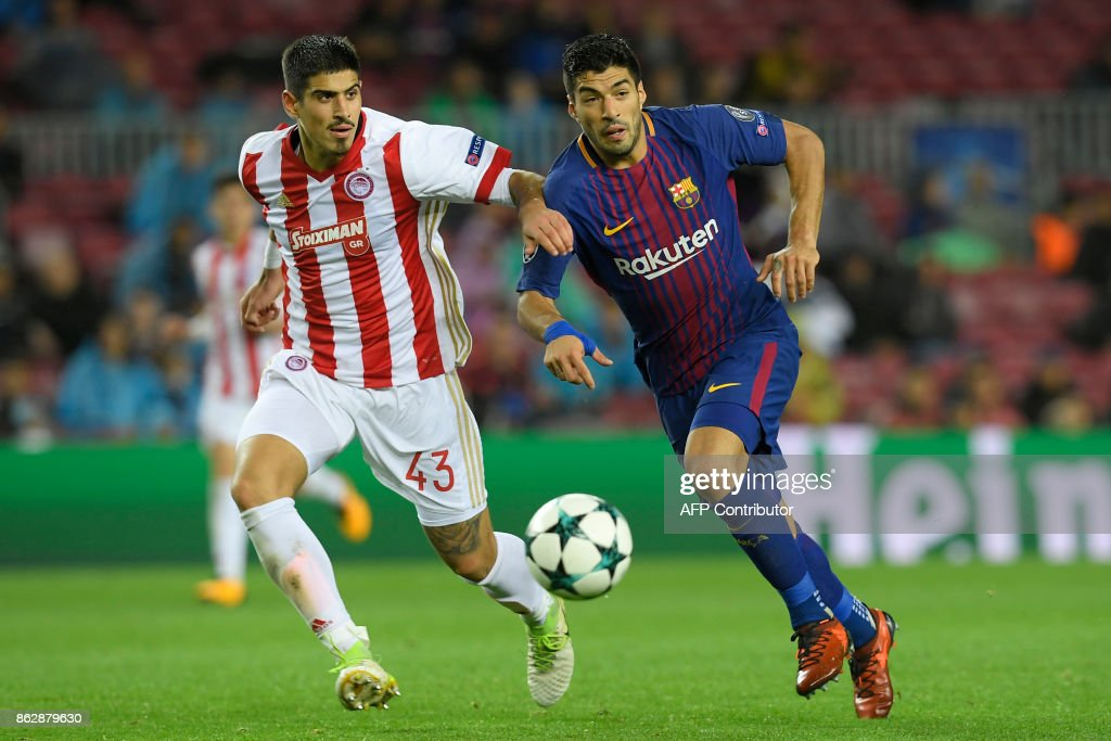 Barcelona's Uruguayan forward Luis Suarez (R) vies with Olympiacos' Greek defender Dimitris Nikolaou during the UEFA Champions League group D football match FC Barcelona vs Olympiacos FC at the Camp Nou stadium in Barcelona on Ocotber 18, 2017. /