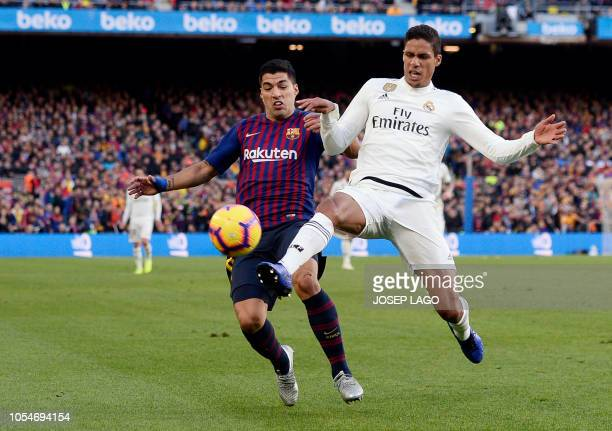 Barcelona's Uruguayan forward Luis Suarez vies with Real Madrid's French defender Raphael Varane during the Spanish league football match between FC...