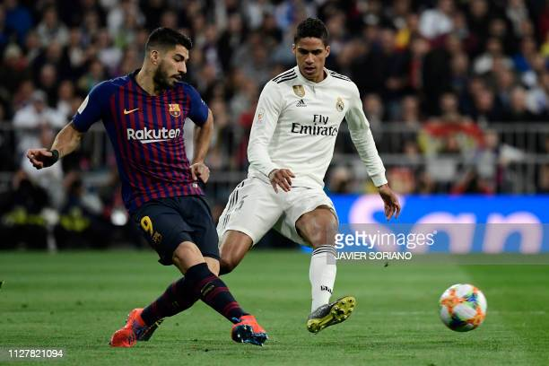 TOPSHOT Barcelona's Uruguayan forward Luis Suarez vies with Real Madrid's French defender Raphael Varane during the Spanish Copa del Rey semifinal...